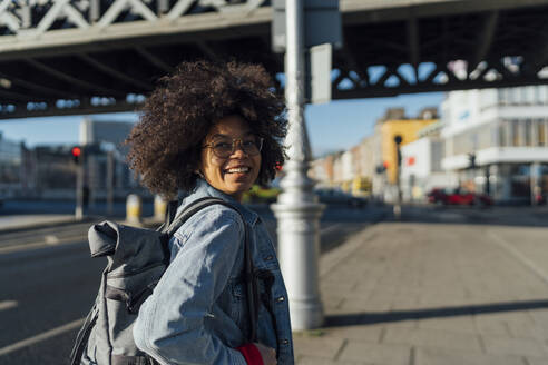 Smiling young woman with afro hair looking away while standing on sidewalk during sunny day - BOYF01458