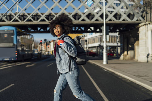 Young woman with afro hair walking on street during sunny day - BOYF01461