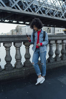Afro young woman using mobile phone while standing on bridge in city - BOYF01464