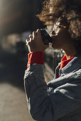 Close-up of afro young woman drinking coffee during sunny day - BOYF01479