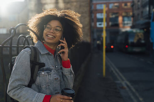 Afro young woman talking over mobile phone while standing on street in city - BOYF01485