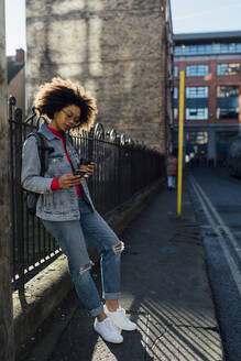 Afro young woman using mobile phone while standing by railing on street in city - BOYF01488