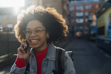 Close-up of cheerful young woman with curly hair talking over smart phone in city - BOYF01491