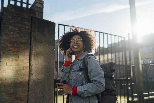 Afro woman talking over mobile phone while standing against sky during sunny day - BOYF01494