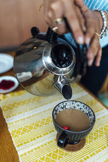 Close-up of young woman pouring water in coffee cup on table at home - BOYF01509