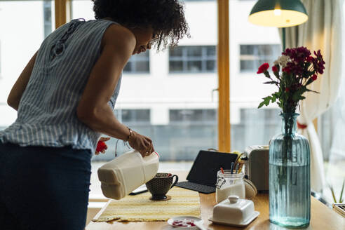 Young woman pouring milk in coffee cup on table at home - BOYF01512