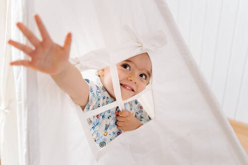 Cheerful little boy in colorful shirt outstretching arm through window of white tent while playing in light nursery at home - ADSF15087
