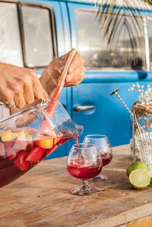 Faceless person pouring cool sangria in crystal glasses on wooden table against blue van on tropical beach - ADSF15093