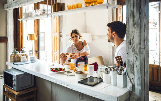Young couple sitting at table and having breakfast at home - EHF00901