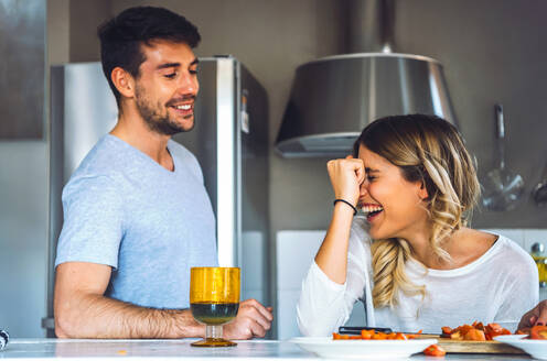 Young female laughing widely standing near smiling man during cooking dinner. - EHF00943