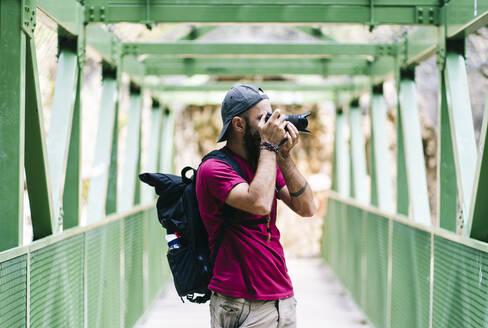 Man taking photo through camera while standing on bridge at Ruta Del Cares, Asturias, Spain - DGOF01406