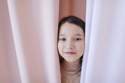 Girl hiding behind curtain at home - OGF00518