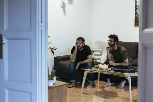 Stressed male friends watching sports while sitting in living room seen through doorway - XLGF00477