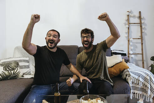Cheerful male spectators screaming while watching sports in living room - XLGF00489
