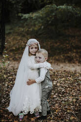 Sister embracing brother at halloween party while standing in forest - GMLF00542