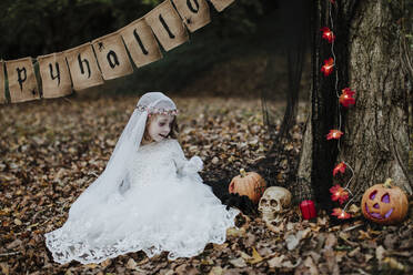 Cute little girl looking at halloween decoration in forest - GMLF00545
