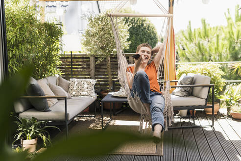 Cheerful mid adult woman talking over smart phone while swinging in porch seen through indoors - UUF21253