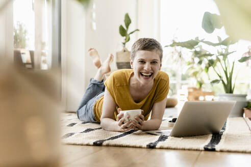 Cheerful woman holding coffee cup while using laptop on carpet at home - UUF21307