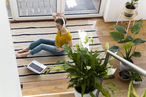 Cheerful woman listening music and dancing while sitting with laptop on carpet at home - UUF21319