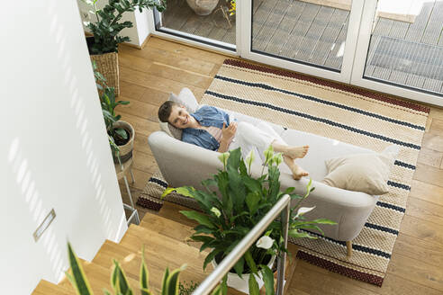 Smiling woman using mobile phone while lying on sofa in living room - UUF21340