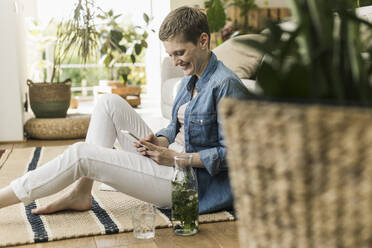 Smiling mid adult woman with short hair using smart phone while sitting on carpet at home - UUF21346
