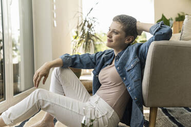 Thoughtful mid adult woman with short hair sitting by armchair at home - UUF21352