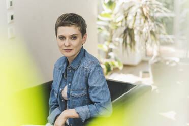 Confident beautiful woman with short hair sitting on armchair at home - UUF21355