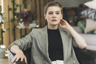 Confident businesswoman wearing blazer sitting on armchair at home - UUF21361