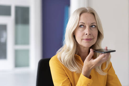 Close-up of businesswoman talking over mobile phone while sitting in home office - MOEF03188