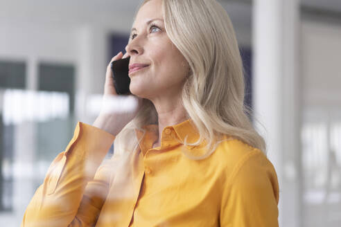 Close-up of businesswoman talking over smart phone in home office seen through window - MOEF03197