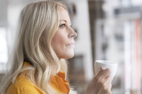 Close-up of thoughtful businesswoman holding coffee cup in home office seen through window - MOEF03200