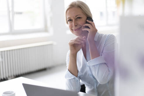 Smiling businesswoman talking over smart phone while sitting at desk in home office - MOEF03212