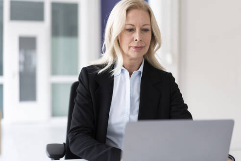 Confident businesswoman working over laptop while sitting at home - MOEF03227