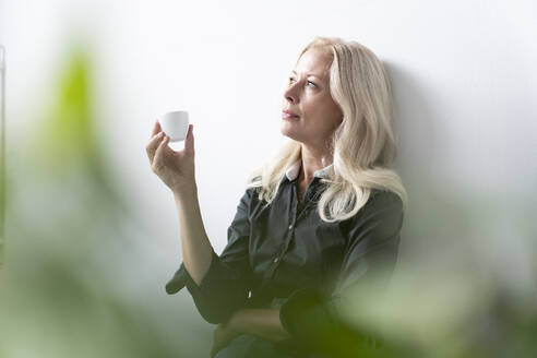 Thoughtful female professional holding coffee cup while sitting against white wall in office - MOEF03260