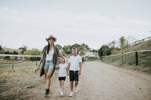 Mother with daughter and son walking on footpath against sky - GMLF00586