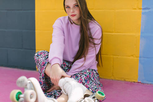 Trendy teenager with roller skates sitting near yellow wall - ADSF15198