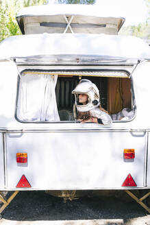 Girl wearing space suit looking through window while sitting in motor home - JCMF01362