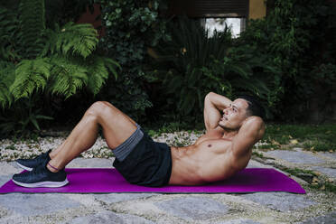 Shirtless athlete with hands behind head exercising on mat against plants in yard - EBBF00694