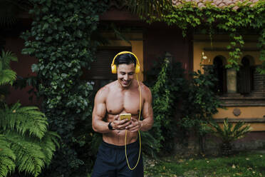 Shirtless mid adult man listening music through headphones while standing in yard - EBBF00700