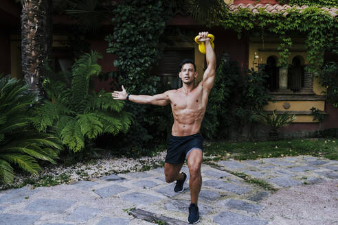 Shirtless man lifting kettlebell while standing against plants in yard - EBBF00712