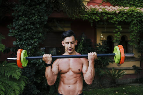 Shirtless mid adult man athlete lifting deadlift while standing in yard - EBBF00718