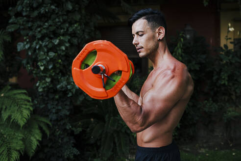 Shirtless male athlete lifting deadlift while standing in yard - EBBF00721