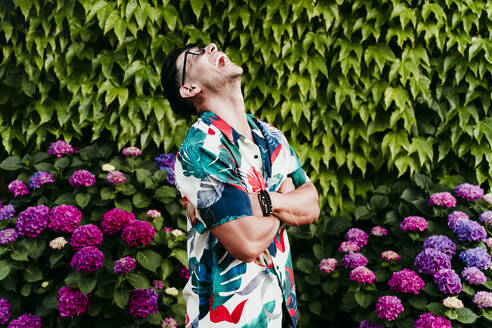 Man with arms crossed laughing while standing against ivy hedge - EBBF00739