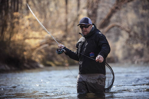 Fly fisherman holding fishing rod while standing in river at forest - DHEF00377