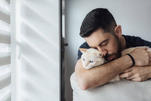 Mid adult man embracing cat in arms while sitting at home - SASF00068