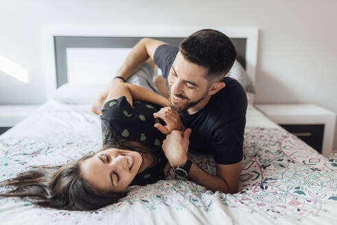 Smiling couple playing on bed in bedroom at home - SASF00080
