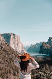 Back view of unrecognizable female traveler in hat standing on hill covered with forest and admiring picturesque scenery with granite cliffs in sunny day in Yosemite National Park in California - ADSF15243