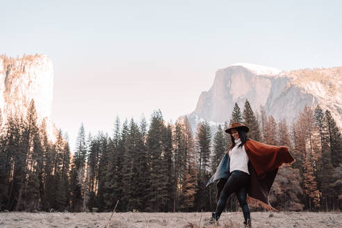 Side view of cheerful young woman in poncho and hat walking on dry grass near forest with granite rocky cliffs in background in sunny day in Yosemite National Park in USA - ADSF15246