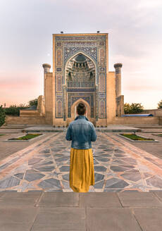 Back view of unrecognizable woman standing in doorway of shabby ornamental building in Samarkand, Uzbekistan - ADSF15261