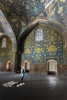 Side view of Muslim female standing in majestic Iranian mosque with ornamental walls covered with colorful mosaic and stained glass windows - ADSF15264